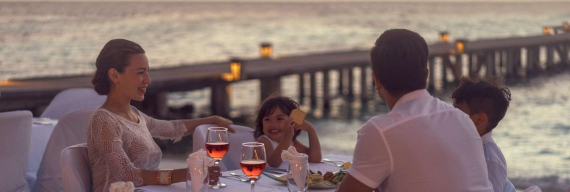 Club Med Kani, Maldives - A family enjoying an evening meal on an outdoor terrace.
