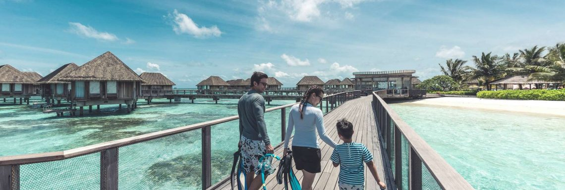 Club Med Kani, Maldives - A family walks on a wooden bridge, overlooking the ocean.
