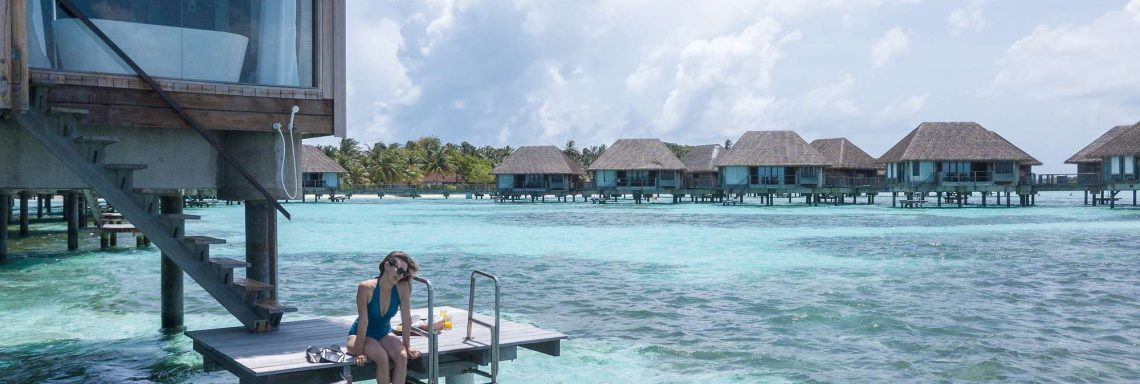 Club Med Kani, Maldives - A couple is on their outdoor balcony and bathes in the Ocean.