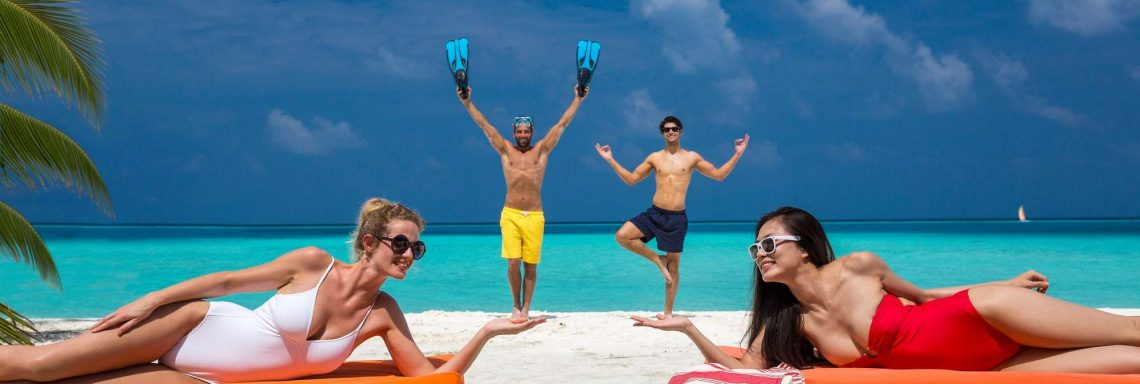 Club Med Kani, Maldives - Four people enjoy the beach on lounge chairs.