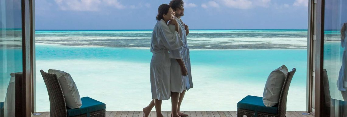 Club Med Villas in FInolhu, Maldives - Photo of a couple on the terrace of a villa in front of the turquoise blue lagoon