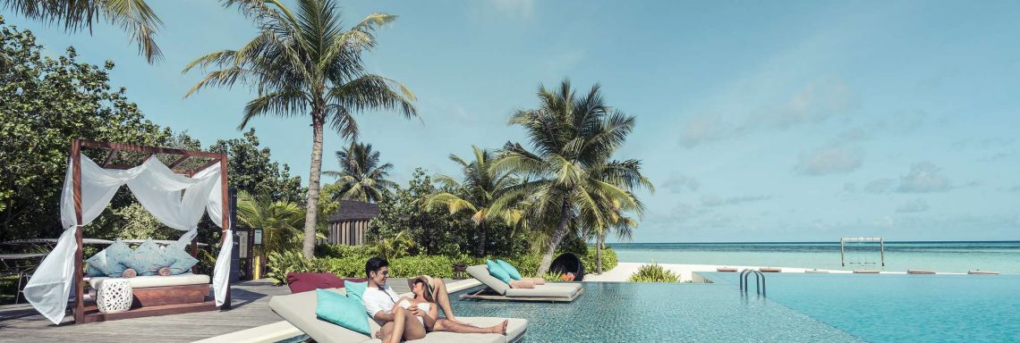 Club Med Villas in FInolhu, Maldives - Photo of a couple on a sofa on the infinity pool in front of the lagoon