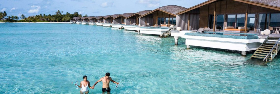 Club Med Villas of FInolhu, Maldives - A couple bathing in the lagoon in front of a villa