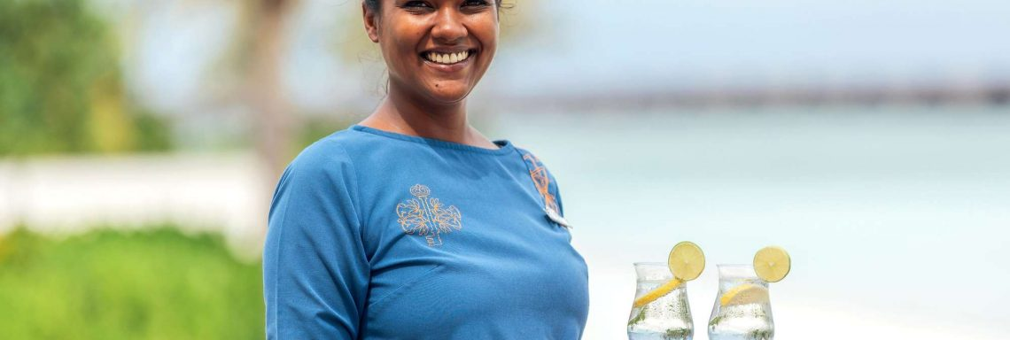 Club Med Villas in FInolhu, Maldives - Photo of a Club Med employee serving cocktails on the beach