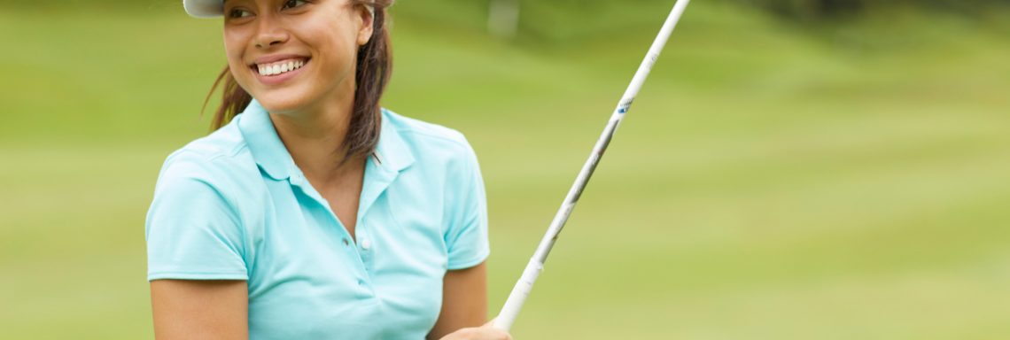Club Med Da Balaia, Portugal - A woman is olding her golf club in her hand and smiling