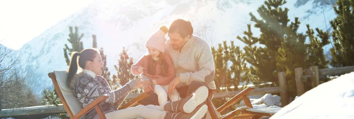 Club Med Cervinia, Italy - A couple with their child sitting on a deck chair