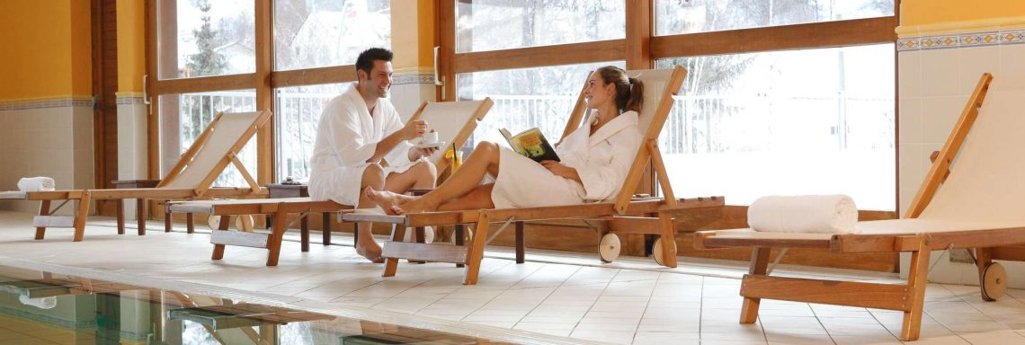 Club Med Serre-Chevalier, France - Image of a couple by the indoor pool with a view of the snowy mountain