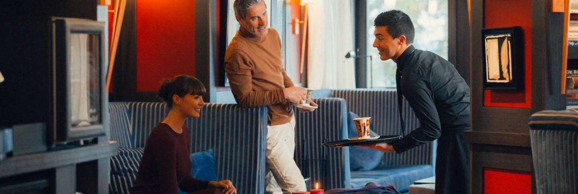 Club Med Valmorel, in France - Image of two people speaking to the waiter in the lounge area