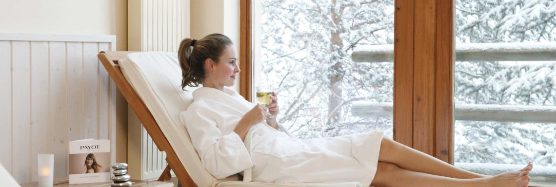 Club Med Serre-Chevalier, in France - Image of a woman in a bathrobe lying on an indoor deckchair with a view of the snowy landscape