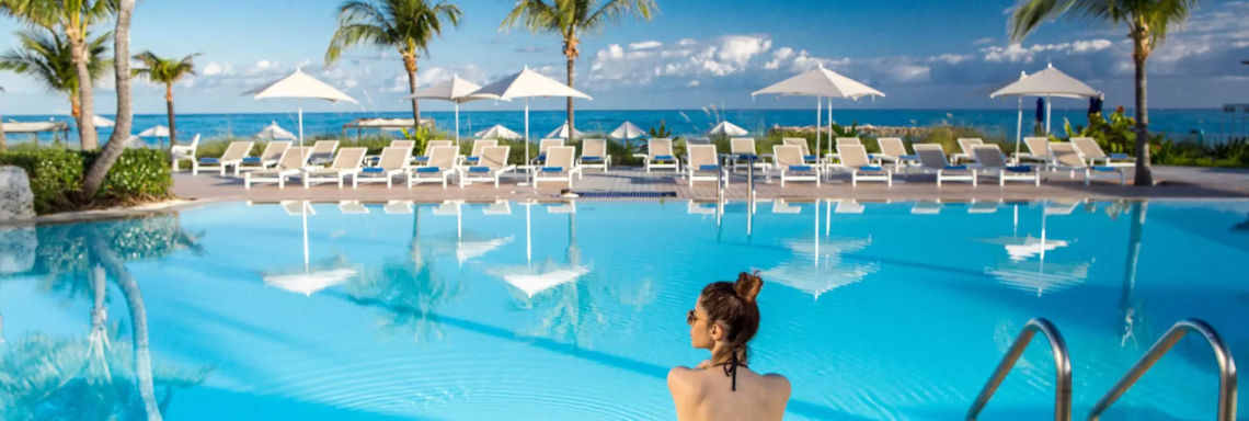 Club Med Columbus Isle, Bahamas - A woman sits by the pool, at the resort, facing the sea